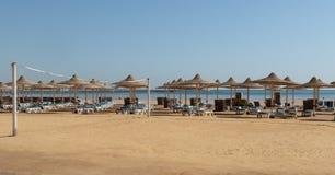 Verlaten strand met sunbeds, paraplu's en een netto volleyball overziend het overzees stock foto's