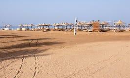 Verlaten strand met voetafdrukken in het zand, sunbeds, paraplu's en een netto volleyball overziend het overzees stock foto's
