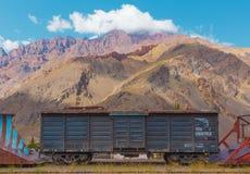 Verlaten trein onder de bergen in de Andes Stock Fotografie