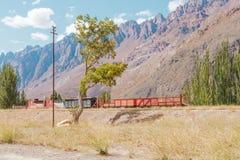 Verlaten trein onder de bergen in de Andes Stock Afbeelding