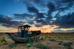 Verlaten vissersboot op strandlandschap bij zonsondergang Stock Afbeelding