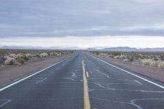 Verlaten Woestijnweg die Doodsvallei verlaten royalty-vrije stock afbeelding