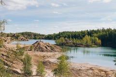Verlaten zandsteengroeve aan het blauwe meer Stock Foto's