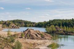 Verlaten zandsteengroeve aan het blauwe meer Stock Foto