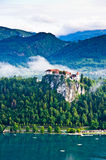 Verlaufenes Schloss zwischen dem See und den Bergen lizenzfreies stockfoto