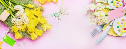 Verlegen Sie Gedeck-MIT-Frühlingsblumen, Tischbesteck, Kuchen, Dekor und leeren Aufkleber auf hellrosa Hintergrund, Draufsicht, F Stockfotografie