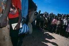 Verlegen Sie Leutewarteschlange für Hilfsmittel in einem Lager in Angola Lizenzfreie Stockfotos