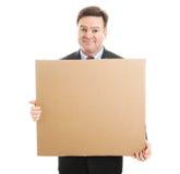 Verlegener Geschäftsmann mit Pappzeichen Stockbilder