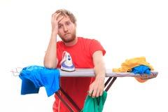 Verlegener Mann bügelt Kleidung an Bord stockfotos