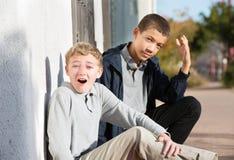 Verlegenes jugendlich mit dem Freund, der schimpflich reagiert Stockbilder
