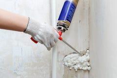 Verlegenheit der Arbeitskraft Handeine Miete in der Wand unter Verwendung des Polyurethanschaums lizenzfreie stockfotografie