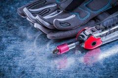 Verlegte Schutzhandschuhe des muunction Schraubenziehergewebes auf Metall Stockfotos