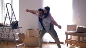 Verlegung zu den Neubauwohnungen, Freudenpaar lacht und Kerl führt Mädchen zurück unter Kästen während des Bewegens auf Wohnung f stock video footage