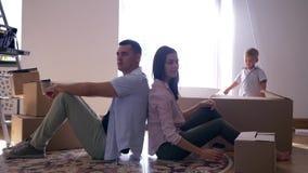 Verlegung zu den Neubauwohnungen, zur jungen Familienfreude flach und zum Getränkkaffee beim Sitzen auf Boden unter Kästen mit Sa stock footage