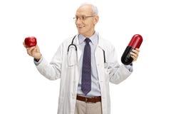 Verleide rijpe arts die een appel en een grote pil houden Stock Afbeeldingen