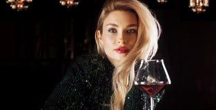 Verleidelijk blonde in het groene avondjurk stellen met een glas rode wijn stock afbeelding