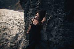 Verleidelijk meisje in de zwarte kleding status die tegen de rots leunen stock afbeelding