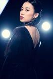 Verleidelijke Aziatische vrouw die in avondtoga camera bij gebeurtenis met schijnwerpers bekijken Stock Fotografie