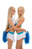 Verleidelijke blonden die in het cheerleading van uniformen stellen Stock Afbeeldingen