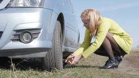 Verleidelijke blondevrouw die veranderingswiel op een auto op landelijke weg proberen 4K stock footage
