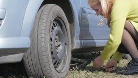 Verleidelijke blondevrouw die veranderingswiel op een auto op landelijke weg proberen 4K stock videobeelden