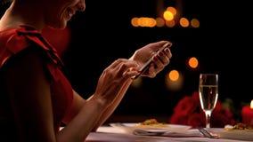 Verleidelijke dame het scrollen smartphone app in restaurant, wachtende mens, afspraak tussen onbekende man en vrouw stock fotografie