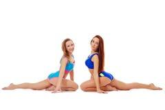 Verleidelijke flexibele meisjes die uitrekkende oefening doen Royalty-vrije Stock Afbeelding