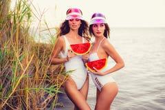 Verleidelijke modellen in zwempakken die met watermeloen stellen stock afbeeldingen