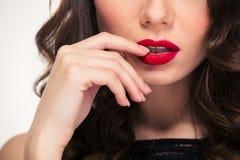 Verleidende rode lippen van krullende die vrouw door haar hand worden geraakt stock foto
