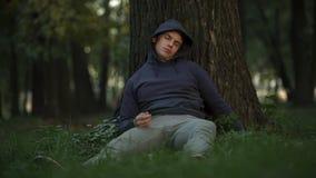 Verletzbarer Alkoholiker, der unter Baum in der Park-, unvorsichtiger und verrückterjugend schläft lizenzfreies stockfoto