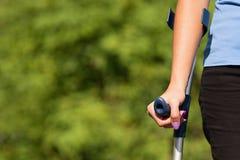 Verletzte Frau, die versucht, auf Krücken zu gehen lizenzfreie stockfotos