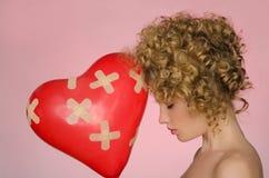 Verletzte Frau mit Ball in Form des Herzens Stockfotografie