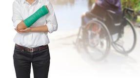 Verletzte Frau mit dem Grün an Hand geworfen und Arm auf blurre lizenzfreies stockfoto