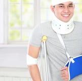 Verletzte Gebrauchskrücke des jungen Mannes und Armriemen lizenzfreie stockfotografie