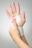 Verletzte Hand mit blutigem Verband Stockbild