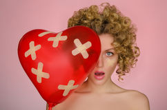 Verletzte junge Frau mit Ball in Form des Herzens Lizenzfreie Stockfotos