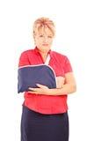 Verletzte reife Frau mit dem gebrochenen Arm, der Kamera betrachtet Stockfotos