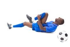 Verletzter Fußballspieler, der aus den Grund liegt Stockbilder
