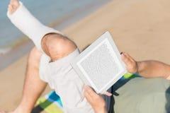 Verletzter Mann, der auf dem Strand sich entspannt Stockbild