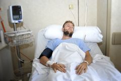 Verletzter Mann, der im Bettkrankenhauszimmer stillsteht von den Schmerz schauen in schlechter Gesundheitszustand liegt Stockfoto