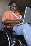 Verletzter Mann, der Laptop verwendet und Musik hört lizenzfreie stockfotos