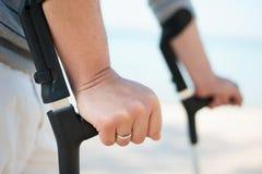 Verletzter Mann, der versucht, auf Krücken zu gehen Lizenzfreie Stockbilder