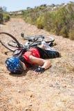 Verletzter Radfahrer, der auf dem Boden nach einem Abbruch liegt Stockbilder