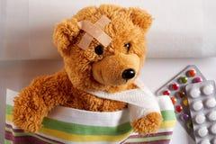 Verletzter Teddybär mit dem Arm in einem Riemen stockbilder
