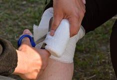 Verletztes Knie erhielt Aufmerksamkeit der ersten Hilfe stockfotos