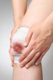 Verletztes Knie mit blutigem Verband Stockbilder