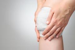 Verletztes Knie mit Verband Stockfoto