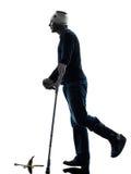 Verletztes unvorsichtiges Gehen des Mannes mit Krückenschattenbild Stockfoto