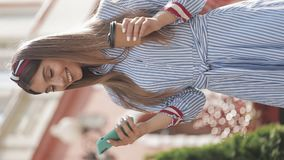 Verlical Video. Beautiful Young Woman with Headband Wearing Stylish Striped Dress Using her Smartphone Scrolling stock footage