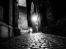 Verlicht cobbled straat in oude 's nachts stad Stock Fotografie